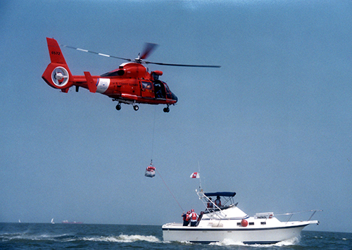 U.S. Coast Guard helicopter hovering over an enforcement boat